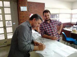 Compañeros firmando la compra de lotes